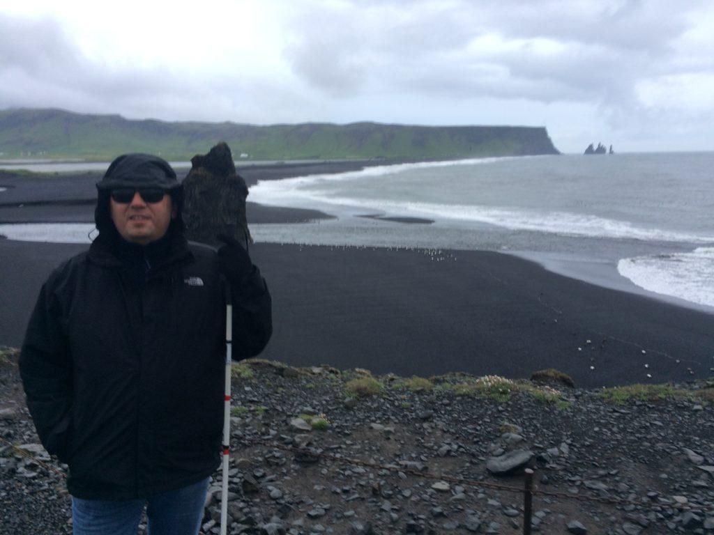 Na zdjęciu ja, na czarnej plaży Reynisfjara w padającym deszczu, ubrany w przeciwdeszczową kurtkę, kaptur i rękawiczki.