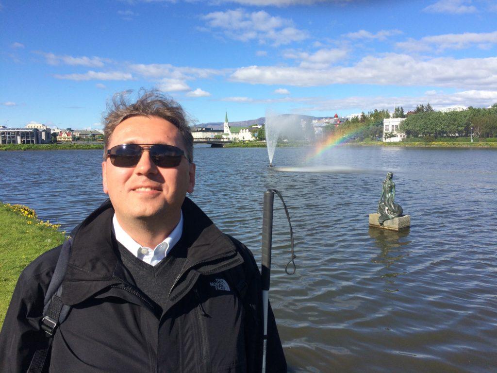 Jestem przed fontanną w jednym z miejskich parków. Krople wody podświetlone słońcem tworzą tęczę za moimi plecami.