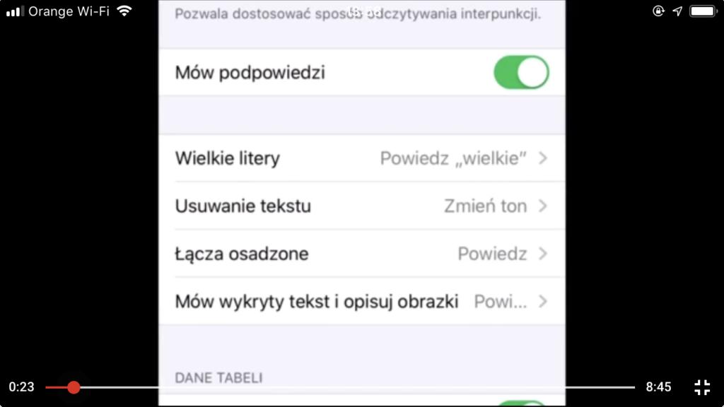 Zrzut ekranu z iPhone - Odtwarzacz z kadrem z nagrania, na którym fokus VoiceOver podświetla funkcję Interpunkcja