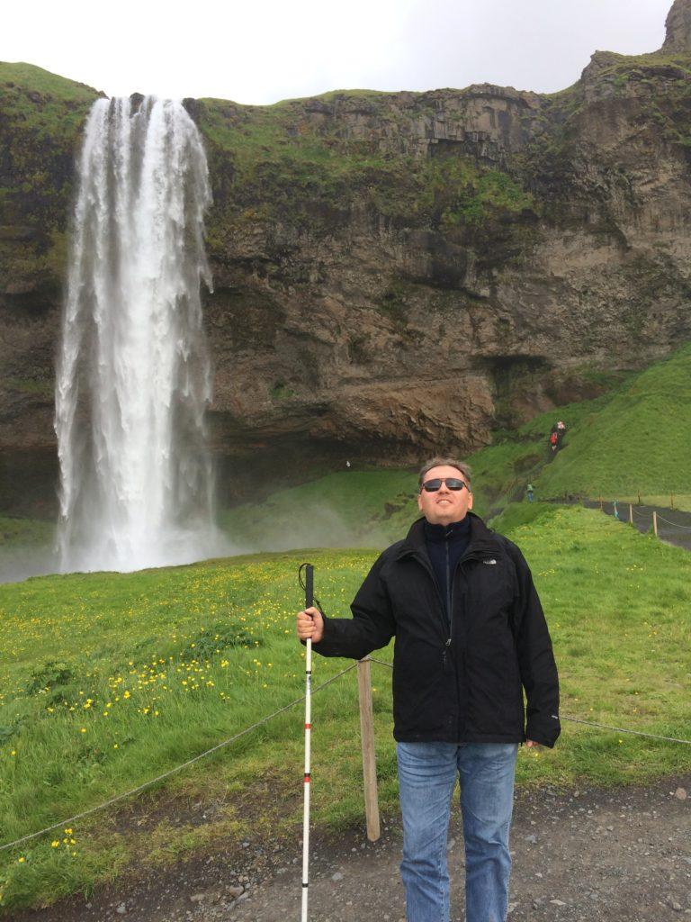 Stoję na tle wodospadu Seljalandsfoss.