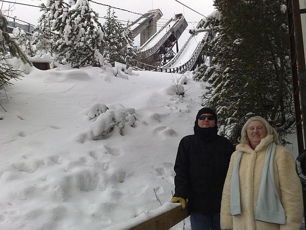 Zimowy, pochmurny dzień w fińskim Lahti. Na zdjęciu, ciepło ubrani, Alicja i Piotr. Za nimi po prawej stronie widać skocznie narciarskie. Wszystko do koła pokryte jest grubą warstwą śniegu.