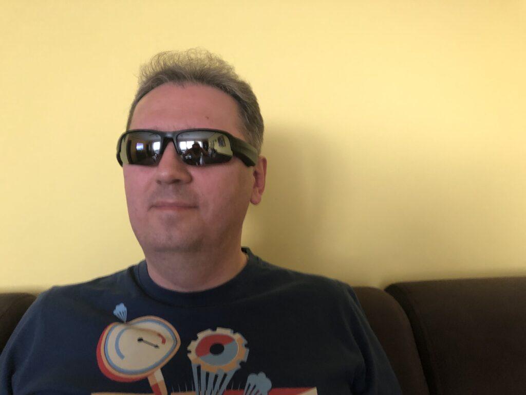 Piotr w granatowej koszulce i ciemnych okularach Bose Frames Tempo