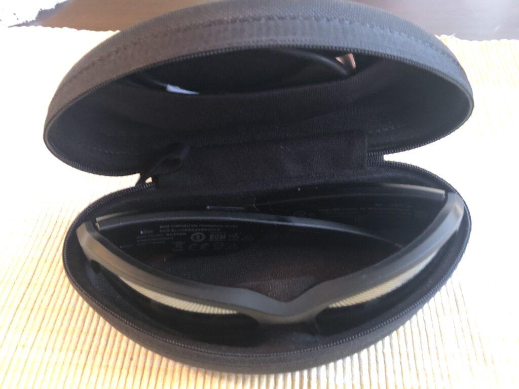 Okulary Bose Frames Tempo leżące w otwartym etui. Na tylnej ściance widać kieszonkę i fragment wystającego z niej kabelka do ładowania.